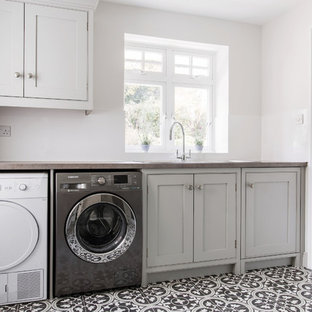 Inspiration for an expansive contemporary u-shaped utility room in Kent with shaker cabinets, grey cabinets, ceramic floors, a side-by-side washer and dryer, a single-bowl sink, laminate benchtops, grey walls, yellow floor and grey benchtop.