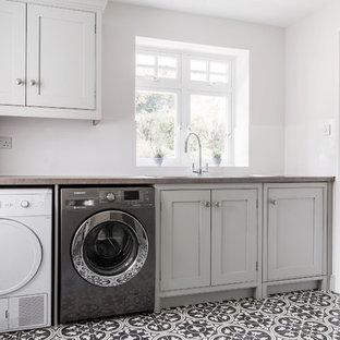 Immagine di un'ampia lavanderia multiuso design con ante in stile shaker, ante grigie, pavimento con piastrelle in ceramica, lavatrice e asciugatrice affiancate, lavello a vasca singola, top in laminato, pareti grigie, pavimento giallo e top grigio