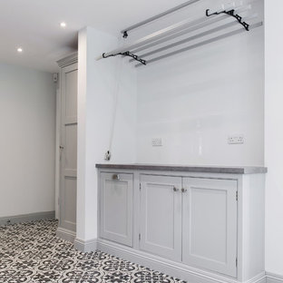 Example of a huge trendy u-shaped ceramic tile and yellow floor utility room design in Kent with shaker cabinets, gray cabinets, a side-by-side washer/dryer, laminate countertops, gray walls and gray countertops