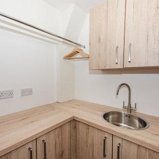 Modern inredning av en tvättstuga, med släta luckor, laminatbänkskiva, stänkskydd i trä, ljust trägolv och skåp i ljust trä