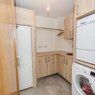 Cette image montre une buanderie minimaliste avec un placard à porte plane, des portes de placard marrons, un plan de travail en stratifié, une crédence en bois et un sol en bois clair.
