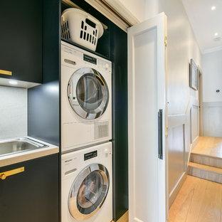 Idéer för en klassisk vita linjär liten tvättstuga, med en nedsänkt diskho, släta luckor, svarta skåp, ljust trägolv, en tvättpelare och beiget golv