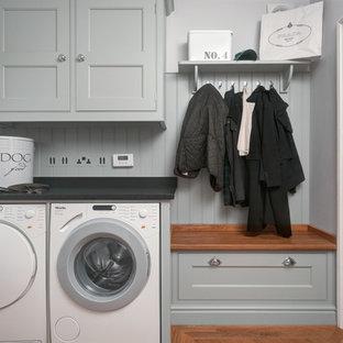 Inredning av ett klassiskt litet svart linjärt svart grovkök, med granitbänkskiva, grå väggar, kalkstensgolv, en tvättmaskin och torktumlare bredvid varandra, luckor med profilerade fronter och grå skåp