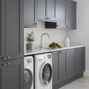 Medium sized classic single-wall utility room in Other with shaker cabinets, grey cabinets, grey walls, porcelain flooring, a side by side washer and dryer, beige floors and white worktops.