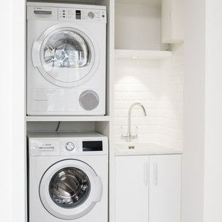 Esempio di una piccola lavanderia design con lavello sottopiano, pareti bianche e pavimento in cemento
