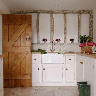 Exemple d'une buanderie parallèle romantique de taille moyenne avec un placard à porte shaker, un évier de ferme, des portes de placard blanches, un plan de travail en bois et un mur blanc.