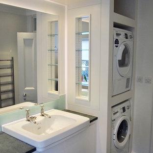 Esempio di una lavanderia multiuso contemporanea di medie dimensioni con lavello da incasso, ante lisce, ante bianche, top in granito, pareti bianche, pavimento in ardesia, lavatrice e asciugatrice a colonna, pavimento verde e top grigio
