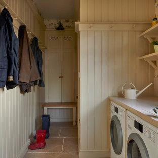 Foto på ett mellanstort lantligt beige parallellt grovkök, med en rustik diskho, luckor med infälld panel, beige skåp, bänkskiva i kvarts, beige stänkskydd, beige väggar, kalkstensgolv, en tvättmaskin och torktumlare bredvid varandra och beiget golv
