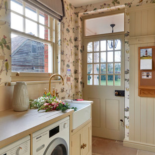 Mid-sized traditional galley utility room in London with a farmhouse sink, recessed-panel cabinets, beige cabinets, quartz benchtops, beige splashback, beige walls, limestone floors, a side-by-side washer and dryer, beige floor, beige benchtop and wallpaper.