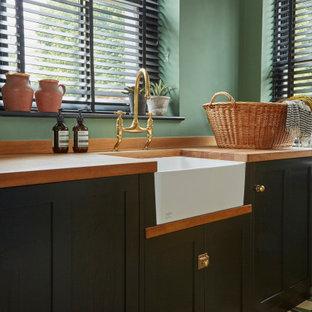 Inredning av en eklektisk tvättstuga, med en rustik diskho, skåp i shakerstil, gröna skåp, träbänkskiva, gröna väggar och grönt golv