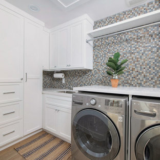Transitional l-shaped medium tone wood floor and brown floor dedicated laundry room photo in Orange County with an undermount sink, shaker cabinets, white cabinets, quartz countertops, multicolored backsplash, mosaic tile backsplash, a side-by-side washer/dryer and white countertops
