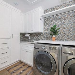 Bild på en vintage vita l-formad vitt tvättstuga enbart för tvätt, med en undermonterad diskho, skåp i shakerstil, vita skåp, bänkskiva i kvarts, flerfärgad stänkskydd, stänkskydd i mosaik, mellanmörkt trägolv, en tvättmaskin och torktumlare bredvid varandra och brunt golv