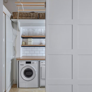 Mid-sized transitional single-wall dedicated laundry room in West Midlands with grey cabinets, wood benchtops, white splashback, subway tile splashback, white walls, an integrated washer and dryer, beige floor and brown benchtop.