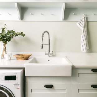 Inspiration for a nautical utility room in London with a belfast sink, shaker cabinets, grey cabinets, grey walls and white worktops.