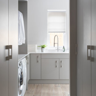 Huge trendy porcelain tile and gray floor laundry room photo in Surrey with an integrated sink, flat-panel cabinets, gray cabinets, quartzite countertops and white countertops