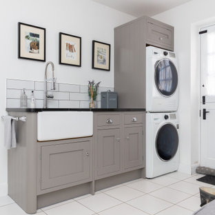 Photo of a transitional single-wall utility room in Other with a farmhouse sink, shaker cabinets, grey cabinets, subway tile splashback, white walls, a stacked washer and dryer, white floor and black benchtop.