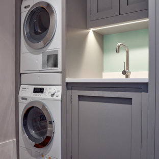 Small contemporary single-wall dedicated laundry room in London with an integrated sink, shaker cabinets, grey cabinets, quartzite benchtops, white walls, dark hardwood floors, a stacked washer and dryer, brown floor and white benchtop.