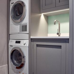 Exempel på en liten modern vita linjär vitt tvättstuga enbart för tvätt, med en integrerad diskho, skåp i shakerstil, grå skåp, bänkskiva i kvartsit, vita väggar, mörkt trägolv, en tvättpelare och brunt golv