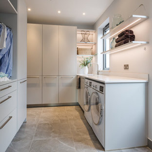 Mid-sized modern u-shaped dedicated laundry room in London with a drop-in sink, flat-panel cabinets, solid surface benchtops, metallic splashback, glass sheet splashback, ceramic floors, brown floor, grey cabinets, white walls, a side-by-side washer and dryer and white benchtop.