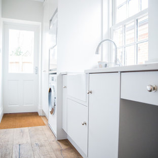 Medium sized modern galley utility room in Berkshire with a belfast sink, flat-panel cabinets, white cabinets, composite countertops, white walls, dark hardwood flooring, a stacked washer and dryer, brown floors and white worktops.