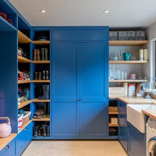Exemple d'une buanderie nature en U multi-usage avec un évier de ferme, un placard à porte shaker, des portes de placard bleues, un plan de travail en bois, un mur jaune, un sol beige et un plan de travail beige.