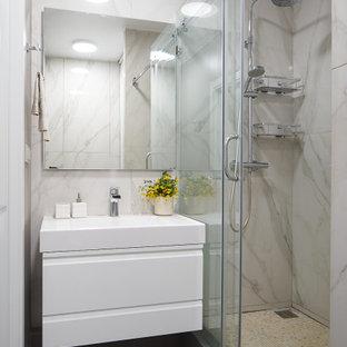 На фото: ванная комната среднего размера в современном стиле с плоскими фасадами, белыми фасадами, душем в нише, серой плиткой, керамогранитной плиткой, полом из керамогранита, душевой кабиной, монолитной раковиной, серым полом, душем с распашными дверями, белой столешницей, тумбой под одну раковину и подвесной тумбой с