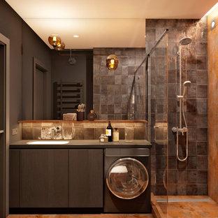 Cette image montre une salle de bain design de taille moyenne avec un placard à porte plane, des portes de placard noires, un carrelage noir, un carrelage gris, un mur noir, un sol en carrelage de porcelaine, un lavabo encastré, un sol orange et un plan de toilette noir.