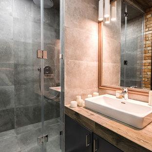 Ejemplo de cuarto de baño con ducha, contemporáneo, de tamaño medio, con armarios tipo vitrina, puertas de armario de madera en tonos medios, ducha a ras de suelo, sanitario de pared, baldosas y/o azulejos marrones, baldosas y/o azulejos de porcelana, paredes grises, suelo de baldosas de porcelana, lavabo encastrado, encimera de azulejos, suelo gris y ducha con puerta con bisagras