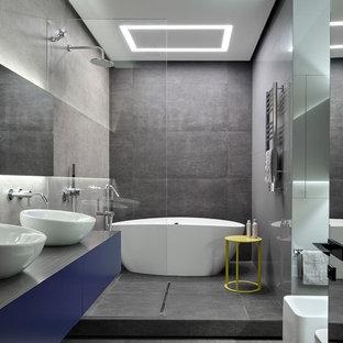 Пример оригинального дизайна: главная ванная комната в современном стиле с душевой комнатой, плоскими фасадами, синими фасадами, отдельно стоящей ванной, инсталляцией, серой плиткой, настольной раковиной и открытым душем