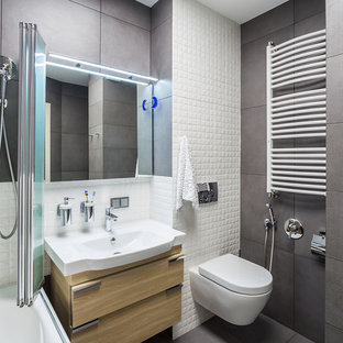 Новый формат декора квартиры: главная ванная комната среднего размера в современном стиле с инсталляцией, серой плиткой, белой плиткой, плоскими фасадами, светлыми деревянными фасадами, душем над ванной, монолитной раковиной и серым полом