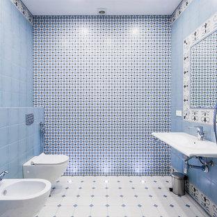 Стильный дизайн: большая ванная комната в современном стиле с биде, керамической плиткой, полом из керамогранита, белым полом, подвесной раковиной, синей плиткой, белой плиткой и синими стенами - последний тренд