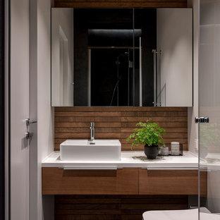 Идея дизайна: ванная комната в современном стиле с плоскими фасадами, фасадами цвета дерева среднего тона, раздельным унитазом, белыми стенами, душевой кабиной, настольной раковиной, черным полом и белой столешницей