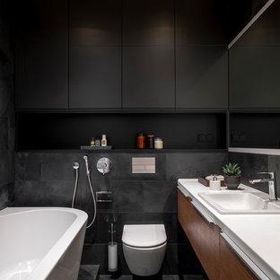 Свежая идея для дизайна: главная ванная комната в современном стиле с плоскими фасадами, фасадами цвета дерева среднего тона, инсталляцией, черной плиткой, накладной раковиной, черным полом и белой столешницей - отличное фото интерьера