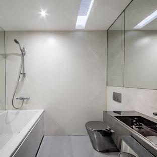 Ispirazione per una piccola stanza da bagno padronale contemporanea con ante grigie, pavimento in cemento, pavimento grigio, vasca ad alcova, piastrelle beige, piastrelle in gres porcellanato, lavabo sospeso, top in acciaio inossidabile e WC a due pezzi
