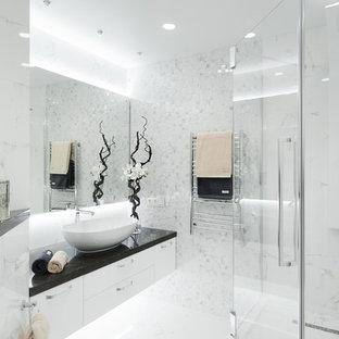 На фото: ванная комната в современном стиле с плоскими фасадами, белыми фасадами, белой плиткой, душевой кабиной, настольной раковиной, белым полом, душем с распашными дверями и черной столешницей с