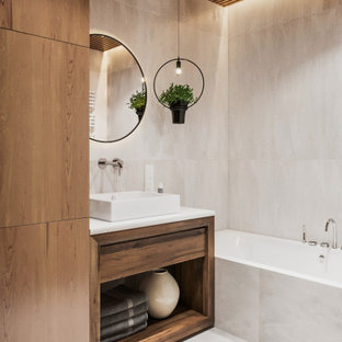 Mid-sized trendy master beige tile and porcelain tile porcelain floor, white floor and wood wall alcove bathtub photo in Other with flat-panel cabinets, medium tone wood cabinets, white walls, solid surface countertops, white countertops and a vessel sink
