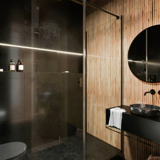 This is an example of a mid-sized contemporary 3/4 bathroom in Other with flat-panel cabinets, black cabinets, a wall-mount toilet, beige tile, porcelain tile, black walls, porcelain floors, solid surface benchtops, black floor, black benchtops, an alcove shower, a vessel sink, a hinged shower door and wood.