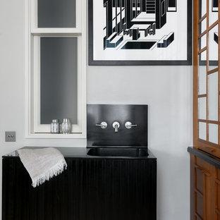 Modelo de cuarto de baño de estilo zen con puertas de armario negras, paredes grises, lavabo integrado y encimeras negras