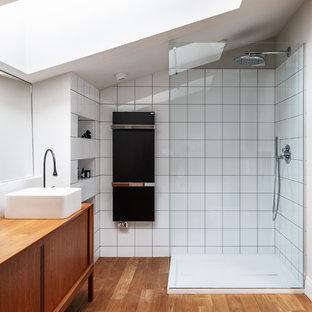На фото: ванные комнаты в современном стиле с фасадами островного типа, фасадами цвета дерева среднего тона, угловым душем, белой плиткой, паркетным полом среднего тона, настольной раковиной и столешницей из дерева