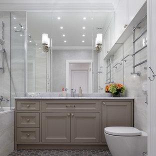 На фото: главная ванная комната в стиле неоклассика (современная классика) с фасадами с утопленной филенкой, серыми фасадами, душем над ванной, серой плиткой, серым полом, открытым душем, серой столешницей, ванной в нише и раздельным унитазом