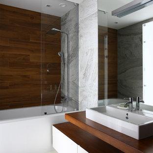 Идея дизайна: главная ванная комната среднего размера в современном стиле с плоскими фасадами, белыми фасадами, полновстраиваемой ванной, серой плиткой, керамогранитной плиткой, столешницей из дерева, душем над ванной, настольной раковиной, открытым душем и коричневой столешницей