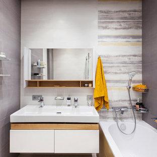 На фото: главные ванные комнаты среднего размера в современном стиле с плоскими фасадами, белыми фасадами, душем над ванной, серой плиткой, керамогранитной плиткой, полом из керамогранита, серым полом, ванной в нише и раковиной с несколькими смесителями