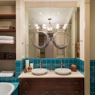 На фото: главная ванная комната в классическом стиле с фасадами цвета дерева среднего тона, накладной ванной, синей плиткой, керамической плиткой, бежевыми стенами, настольной раковиной и фасадами с утопленной филенкой с