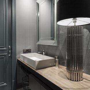 На фото: ванная комната в современном стиле с ванной в нише, серой плиткой, серыми стенами, настольной раковиной и серым полом