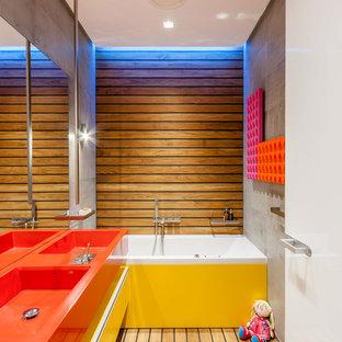 Modernes Kinderbad mit integriertem Waschbecken, flächenbündigen Schrankfronten, gelben Schränken, Badewanne in Nische und hellem Holzboden in Sonstige