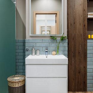 На фото: ванные комнаты в современном стиле с белыми фасадами, синей плиткой, бежевыми стенами, монолитной раковиной и коричневым полом