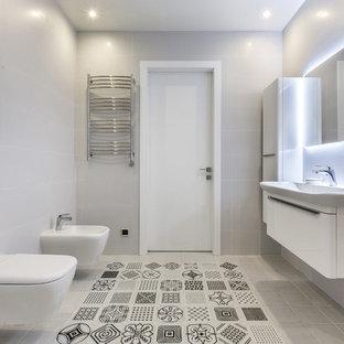 Свежая идея для дизайна: ванная комната в современном стиле с плоскими фасадами, белыми фасадами, биде, серой плиткой и монолитной раковиной - отличное фото интерьера