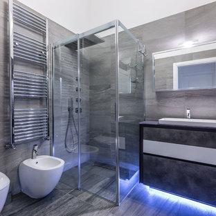 Пример оригинального дизайна: ванная комната среднего размера в современном стиле с плоскими фасадами, серыми фасадами, угловым душем, серой плиткой, плиткой из листового камня, белыми стенами, полом из керамогранита, душевой кабиной, раковиной с несколькими смесителями, стеклянной столешницей и душем с раздвижными дверями