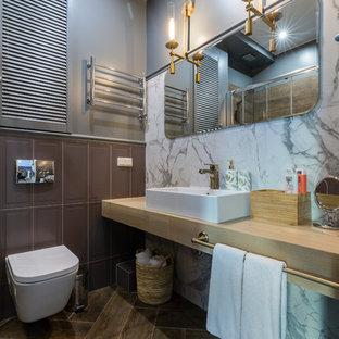 Идея дизайна: ванная комната в современном стиле с инсталляцией, серой плиткой, белой плиткой, серыми стенами, настольной раковиной, коричневым полом и бежевой столешницей