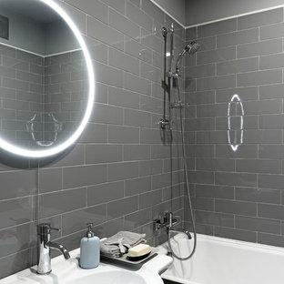 Создайте стильный интерьер: главная ванная комната в стиле современная классика с белыми фасадами, ванной в нише, душем над ванной, серой плиткой, серыми стенами, плиткой кабанчик и консольной раковиной - последний тренд